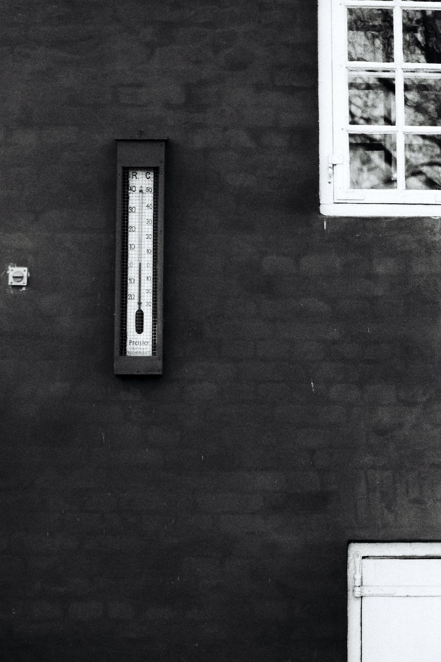 grayscale photography of thermometer on wall