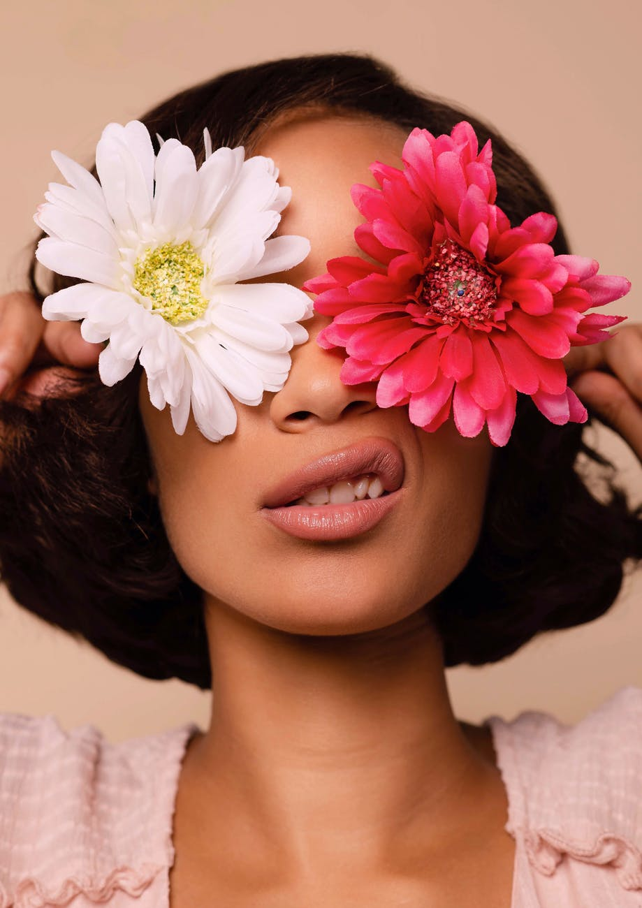 woman holding two flowers across her eyes
